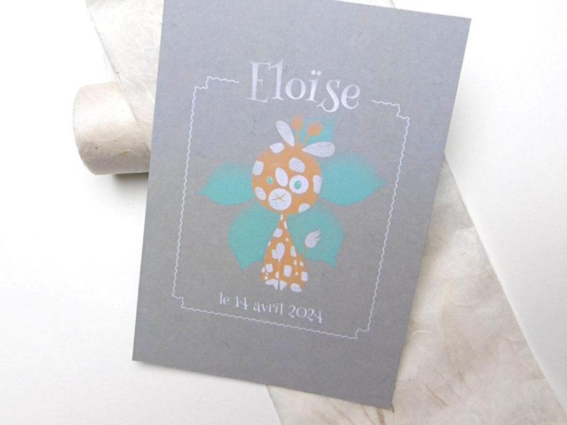 Un doudou girafon auréolé d'une fleur bleu
